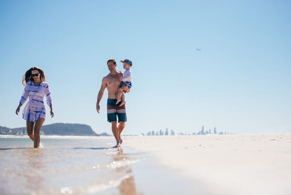 man, woman & child on Gold Coast beach